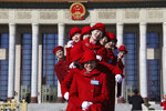 In this March 12, 2019, photo, Chinese bus ushers pose for photos outside the Great Hall of the People during a plenary session of the National People's Congress held in Beijing, China. The country's top judge and head prosecutor delivered reports to the nearly 3,000 members of the ceremonial legislature on their accomplishments over the past year in curbing crime and prosecuting wrong doers, along with their plans for the year ahead. (AP Photo/Ng Han Guan)