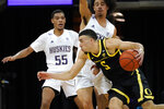 Oregon's Chris Duarte (5) tries to get past Washington's Quade Green (55) and Nate Pryor during the first half of an NCAA college basketball game Saturday, Dec. 12, 2020, in Seattle. (AP Photo/Elaine Thompson)