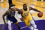 Los Angeles Lakers' LeBron James, right, dribbles past Golden State Warriors' Kelly Oubre Jr. during the first half of an NBA basketball game, Monday, Jan. 18, 2021, in Los Angeles. (AP Photo/Jae C. Hong)