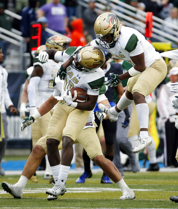UAB cornerback Duke Culver, right, jumps on cornerback Dy'jonn Turner (14) after Turner intercepted a pass against Middle Tennessee in the second half of the NCAA Conference USA championship college football game Saturday, Dec. 1, 2018, in Murfreesboro, Tenn. UAB won 27-25. (AP Photo/Mark Humphrey)