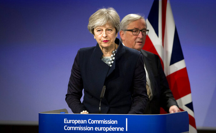 In this Monday, Dec. 4, 2017 file photo, European Commission President Jean-Claude Juncker, right, walks behind British Prime Minister Theresa May prior to addressing a media conference at EU headquarters in Brussels. As May announced her departure with a Brexit plan nowhere near success, European Union leaders offered kind words. But it was quite another matter during the years of negotiations with the bloc that often produced exasperation, miscommunication and even some ridicule of her. (AP Photo/Virginia Mayo, File)