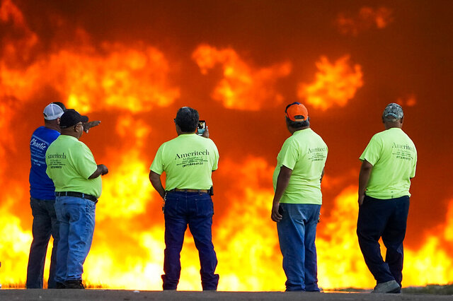 Employees at Ameritech Millworks watch a wall of flames as fire crews battle a massive blaze in an industrial area of Grand Prairie, Texas, in the early morning hours of Wednesday, Aug. 19, 2020. A large fire continues to burn at a Dallas-area factory that makes trash bags and other plastics. Authorities say there are no reports of injuries in the fire at the Poly-America factory. (Smiley N. Pool/The Dallas Morning News via AP)