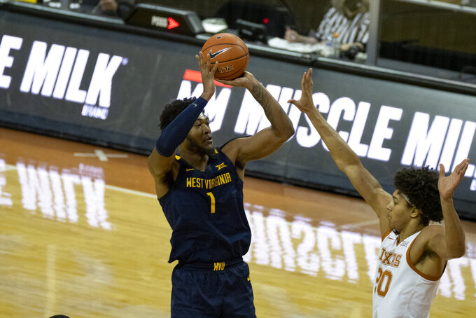 West Virginia forward Derek Culver (1) shoots over Texas forward Jericho Sims (20) during the second half of an NCAA college basketball game, Saturday, Feb. 20, 2021, in Austin, Texas.  (AP Photo/Michael Thomas)