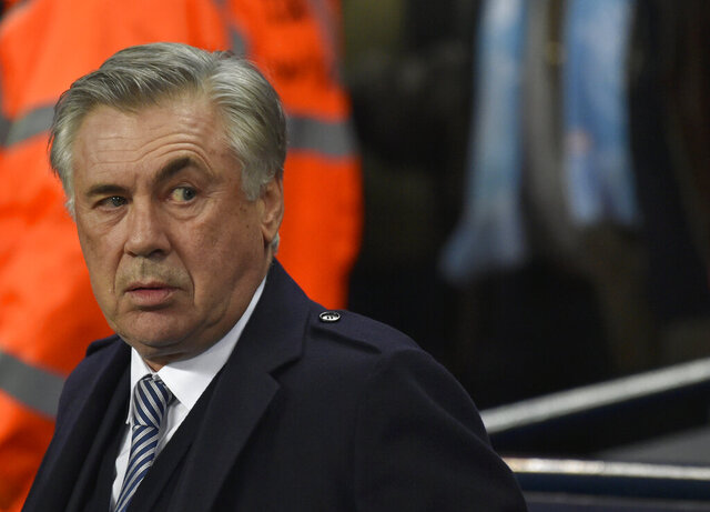 Everton's manager Carlo Ancelotti looks out from the bench before the English Premier League soccer match between Manchester City and Everton at Etihad stadium in Manchester, England, Wednesday, Jan. 1, 2020. (AP Photo/Rui Vieira)