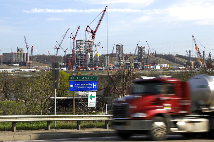 FILE - In this April 18, 2019 file photo a tanker truck passes a petrochemical plant being built on the banks of the Ohio River in Monaca, Pa., for the Royal Dutch Shell company. The plant, which is capable of producing 1.6 million tons of raw plastic annually, is expected to begin operations by 2021. (AP Photo/Gene J. Puskar, File)