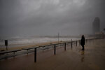 A man looks at the Mediterranean sea during a storm in Barcelona, Spain, Tuesday, Jan. 21, 2020. A winter storm lashed much of Spain for a third day Tuesday, leaving 200,000 people without electricity, schools closed and roads blocked by snow as it killed four people. Massive waves and gale-force winds smashed into seafront towns, damaging many shops and restaurants. (AP Photo/Emilio Morenatti)
