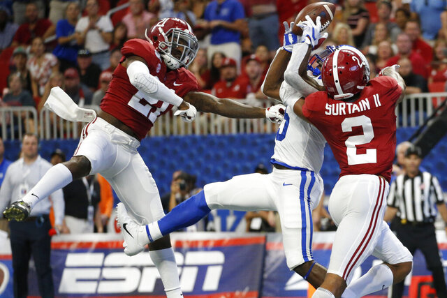 FILE - In this Aug. 31, 2019, file photo, Alabama defensive backs Jared Mayden (21) and Patrick Surtain II (2) break up a pass intended for Duke wide receiver Jalon Calhoun (5) during the first half an NCAA college football game, in Atlanta. Around the country schools are taking the first cautious and detailed steps toward playing football through a pandemic, attempting to build COVID-19-free bubbles around their teams as players begin voluntary workouts throughout June. Thousands of athletes will be tested for COVID-19 _ though not all. (AP Photo/John Bazemore, File)