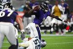 Baltimore Ravens quarterback Tyler Huntley passes under pressure from Carolina Panthers linebacker Christian Miller during the first half of a preseason NFL football game Saturday, Aug. 21, 2021, in Charlotte, N.C. (AP Photo/Jacob Kupferman)