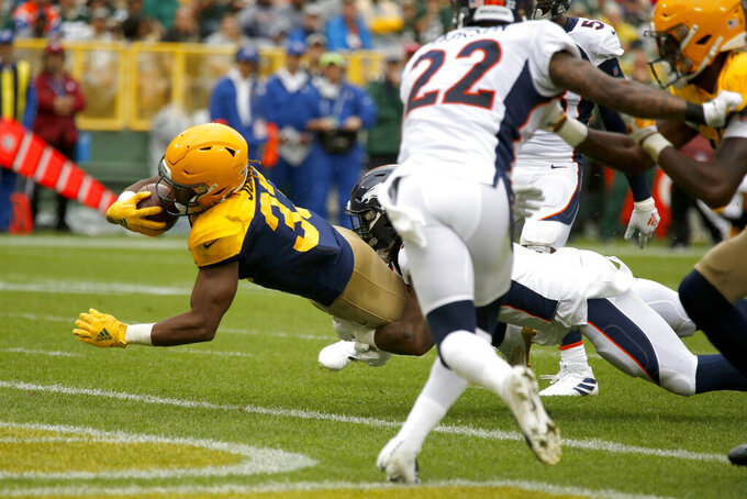 Green Bay Packers running back Aaron Jones, left, scores past Denver Broncos defensive back Kareem Jackson (22) during the first half of an NFL football game Sunday, Sept. 22, 2019, in Green Bay, Wis. (AP Photo/Matt Ludtke)