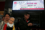 People walk past an electronic board showing Hong Kong share index outside a bank in Hong Kong, Wednesday, Feb. 20, 2019. Shares were mostly higher in Asia on Wednesday after a modestly high finish on Wall Street that extended the market's gains into a fourth week.(AP Photo/Kin Cheung)