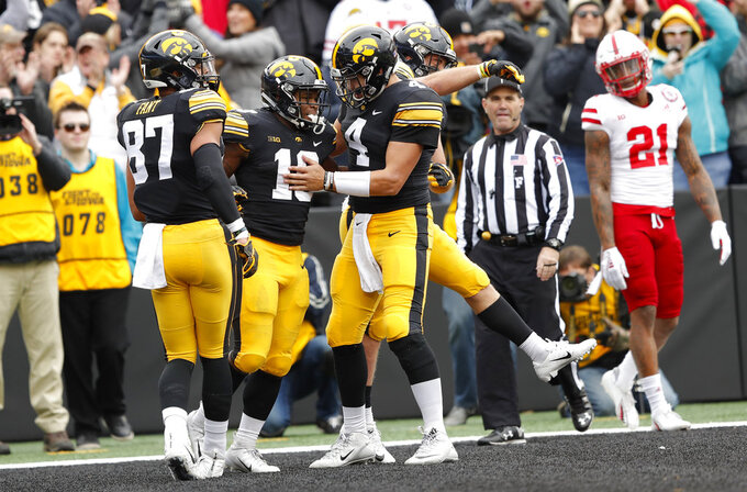 Iowa running back Mekhi Sargent (10) celebrates with teammates Noah Fant, left, and Nate Stanley (4) after scoring on a 15-yard touchdown run during the first half of an NCAA college football game against Nebraska, Friday, Nov. 23, 2018, in Iowa City, Iowa. (AP Photo/Charlie Neibergall)