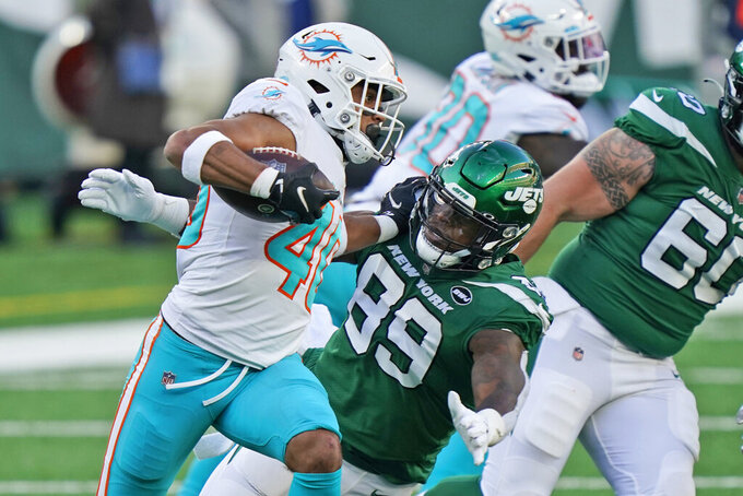 Miami Dolphins' Nik Needham, left, runs the ball after intercepting a throw by New York Jets' quarterback Sam Darnold during the second half of an NFL football game, Sunday, Nov. 29, 2020, in East Rutherford, N.J. (AP Photo/Corey Sipkin)