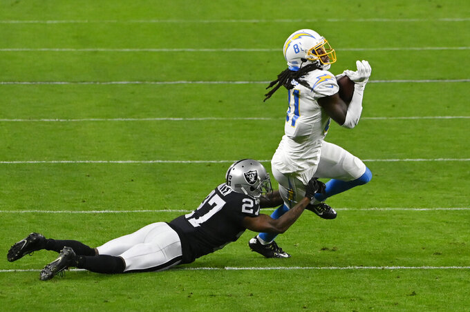 Las Vegas Raiders cornerback Trayvon Mullen (27) tackles Los Angeles Chargers wide receiver Mike Williams (81) during the first half of an NFL football game, Thursday, Dec. 17, 2020, in Las Vegas. (AP Photo/David Becker)