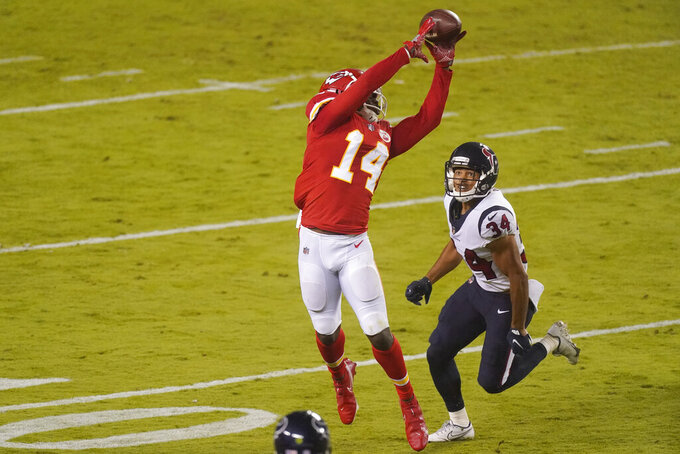 Kansas City Chiefs wide receiver Sammy Watkins (14) catches a pass over Houston Texans cornerback John Reid (34) in the first half of an NFL football game Thursday, Sept. 10, 2020, in Kansas City, Mo. (AP Photo/Charlie Riedel)