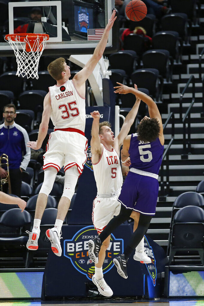 Utah's Branden Carlson (35) and Jaxon Brenchley (5) defend against Weber State guard Cody John (5) as he shoots in the second half during an NCAA college basketball game Saturday, Dec. 14, 2019, in Salt Lake City. (AP Photo/Rick Bowmer)