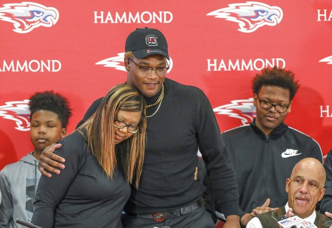 In this Dec. 18, 2019 photo, Hammond's Jordan Burch hugs his mom, Henri Burch, after announcing that he would attend South Carolina to play football during a signing day event in Columbia. S.C. The-6-foot-5, 275-pound Burch is a potential immediate-impact player out for the Gamecocks. When the early signing period opened in December he announced he would stay close to home. But he didn't actually sign, leaving open the possibility LSU could be his final destination. (Tracy Glanz/The State via AP)