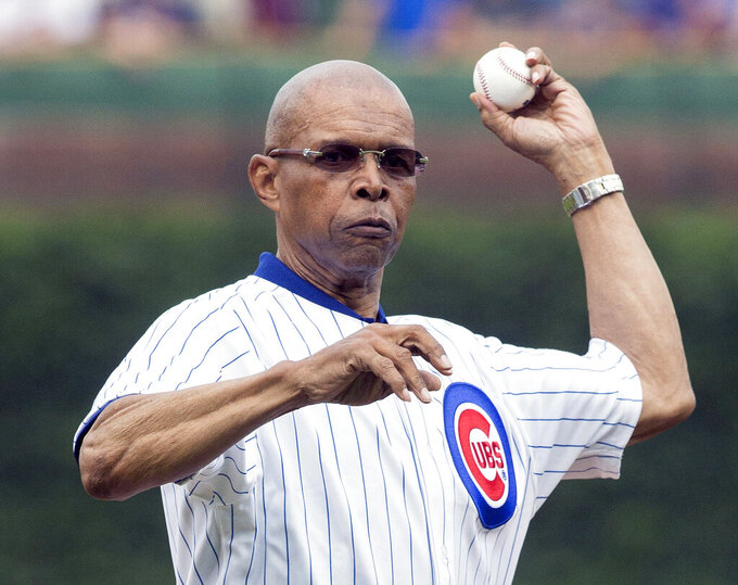 """FILE - In this July 11, 2014, file photo, former Chicago Bears NFL football player Gale Sayers throws out a ceremonial first pitch before a baseball game between the Chicago Cubs and Atlanta Braves, in Chicago. Hall of Famer Gale Sayers, who made his mark as one of the NFL's best all-purpose running backs and was later celebrated for his enduring friendship with Chicago Bears teammate Brian Piccolo, has died. He was 77. Nicknamed """"The Kansas Comet"""" and considered among the best open-field runners the game has ever seen, Sayers died Wednesday, Sept. 23, 2020, according to the Pro Football Hall of Fame. (AP Photo/Andrew A. Nelles, FIle)"""