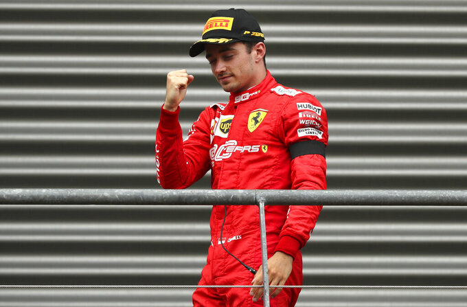 Ferrari driver Charles Leclerc of Monaco pumps his fist as he walks to the podium after finishing first in the Belgian Formula One Grand Prix in Spa-Francorchamps, Belgium, Sunday, Sept. 1, 2019. Mercedes driver Lewis Hamilton of Britain placed second and Mercedes driver Valtteri Bottas of Finland placed third. (AP Photo/Francisco Seco)