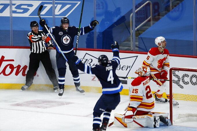 Winnipeg Jets' Patrik Laine (29) celebrates his overtime goal with Neal Pionk (4), as Calgary Flames goaltender Jacob Markstrom (25) and Flames' Mark Giordano (5) react during an NHL hockey game Thursday, Jan. 14, 2021, in Winnipeg, Manitoba. (John Woods/The Canadian Press via AP)