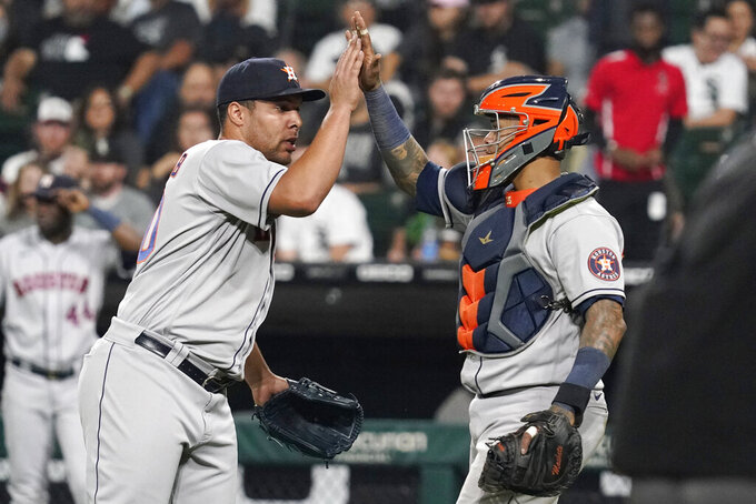 Houston Astros relief pitcher Andre Scrubb, left, celebrates with catcher Martin Maldonado after the Astros defeated the Chicago White Sox 7-1 in a baseball game in Chicago, Friday, July 16, 2021. (AP Photo/Nam Y. Huh)