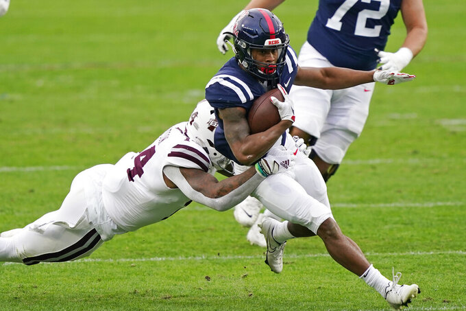 Mississippi running back Jerrion Ealy (9) is tackled by Mississippi State linebacker Nathaniel Watson (14) during the first half of an NCAA college football game, Saturday, Nov. 28, 2020, in Oxford, Miss. (AP Photo/Rogelio V. Solis)