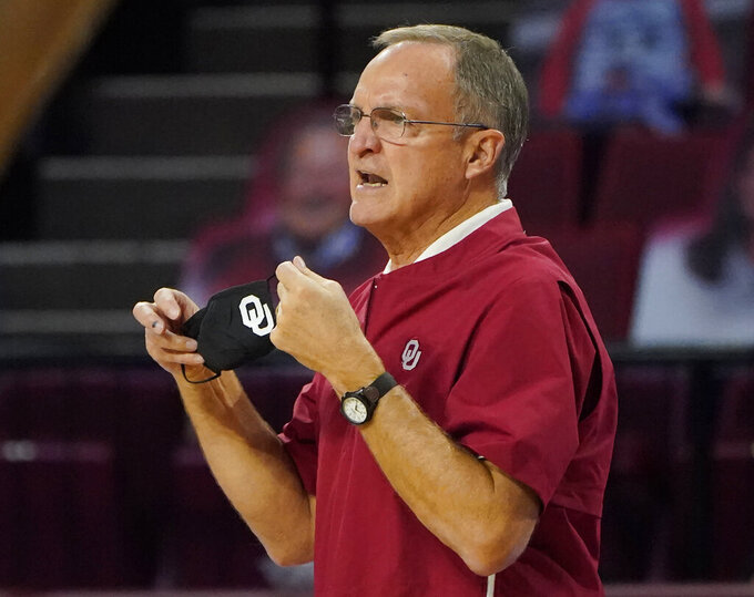 FILE - In this Dec. 3, 2020, file photo, Oklahoma head coach Lon Kruger directs his team in the second half of an NCAA college basketball game against UTSA in Norman, Okla. While many elderly people are isolating at home, college basketball coaches are required to travel, work indoors and be around crowds -- all among the most risky behaviors in the pandemic. Kruger knows he is taking a chance. Oklahoma's 68-year-old has been spared so far, even with his Sooners having to briefly shut down because of cases within the program. (AP Photo/Sue Ogrocki, File)