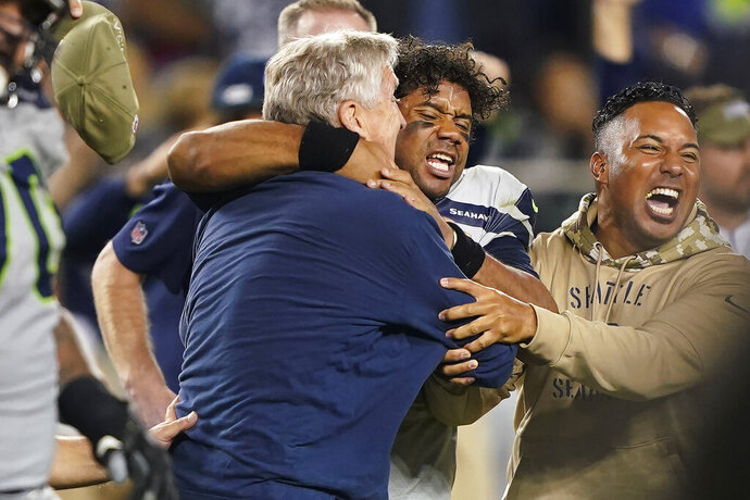 Seattle Seahawks head coach Pete Carroll, left, celebrates with quarterback Russell Wilson, center, after the Seahawks defeated the San Francisco 49ers 27-24 in overtime of an NFL football game in Santa Clara, Calif., Monday, Nov. 11, 2019. (AP Photo/Tony Avelar)