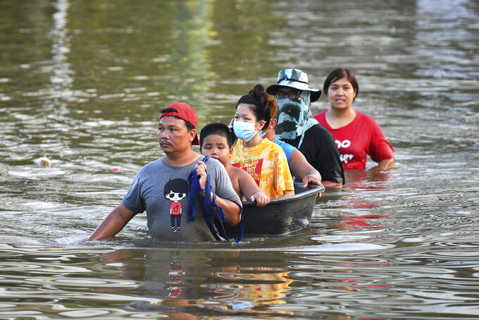 Thai people wade through floodwaters in Chaiyaphum province, northeast of Bangkok, Thailand, Tuesday, Sept. 28, 2021. Thai disaster officials say flooding caused by seasonal monsoon rains have affected more than 71,000 households in 30 provinces and killed six people since the weekend. (AP Photo/Thanachote Thanawikran)