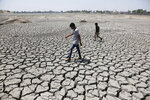 FILE - In this May 14, 2016, file photo, boys on their way to play cricket walk through a dried patch of Chandola Lake in Ahmadabad, India. The decade that just ended was by far the hottest ever measured on Earth, capped off by the second-warmest year on record, NASA and the National Oceanic and Atmospheric Administration reported Wednesday, Jan. 15, 2020. (AP Photo/Ajit Solanki, File)