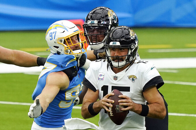 Jacksonville Jaguars quarterback Gardner Minshew, right, is sacked by Los Angeles Chargers defensive end Joey Bosa, left, during the first half of an NFL football game Sunday, Oct. 25, 2020, in Inglewood, Calif. (AP Photo/Alex Gallardo)