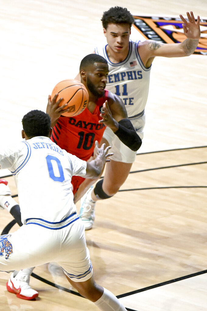 Dayton guard Jalen Crutcher (10) drives between Memphis forward D.J. Jeffries (0) and guard Lester Quinones (11) in the first half of an NCAA college basketball game in the first round of the NIT Tournament, Saturday, March 20, 2021, in Denton, Texas. (AP Photo/Matt Strasen)