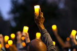 Marchers hold candles up as they listen to a speaker during a march and candlelight vigil for Ahmaud Arbery in the Satilla Shores neighborhood, Tuesday, Feb. 23, 2021, in Brunswick, Ga. Arbery was shot and killed last year while running in the neighborhood. (AP Photo/Stephen B. Morton)