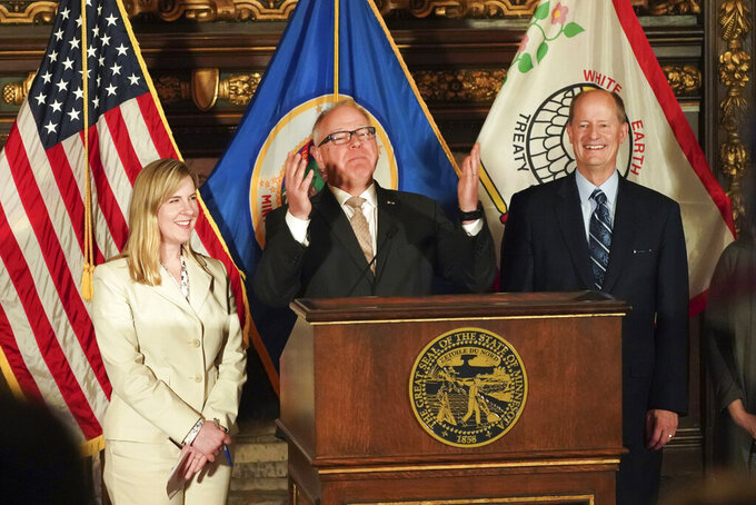 FILE - In this May 19, 2019 file photo, Gov. Tim Walz, center, with Senate Majority Leader Paul Gazelka, right, and House Speaker Melissa Hortman, gestures at a news conference in St. Paul, Minn. When the Minnesota Legislature convenes for its 2021 regular session Tuesday, Jan. 5, 2021, it won't look like a normal session. The House will meet entirely via Zoom until further notice because of the pandemic. The Senate will try a hybrid approach. And the Capitol will remain surrounded by riot fencing. (Glen Stubbe/Star Tribune via AP, File)