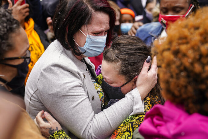 Courtney Ross, girlfriend of the deceased George Floyd, left, hugs Katie Wright, mother of the deceased Daunte Wright, right, before a news conference, Tuesday, April 13, 2021, in Minneapolis. Daunte Wright, 20, was shot and killed by police Sunday after a traffic stop in Brooklyn Center, Minn. (AP Photo/John Minchillo)