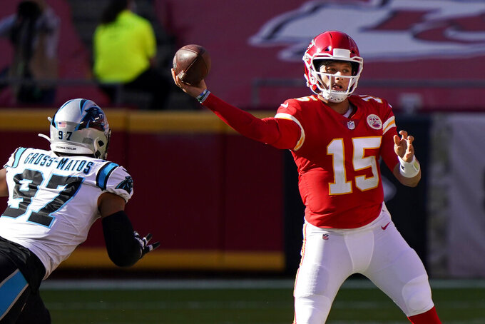 Kansas City Chiefs quarterback Patrick Mahomes (15) passes as Carolina Panthers defensive end Yetur Gross-Matos (97) applies pressure during the second half of an NFL football game in Kansas City, Mo., Sunday, Nov. 8, 2020. (AP Photo/Jeff Roberson)