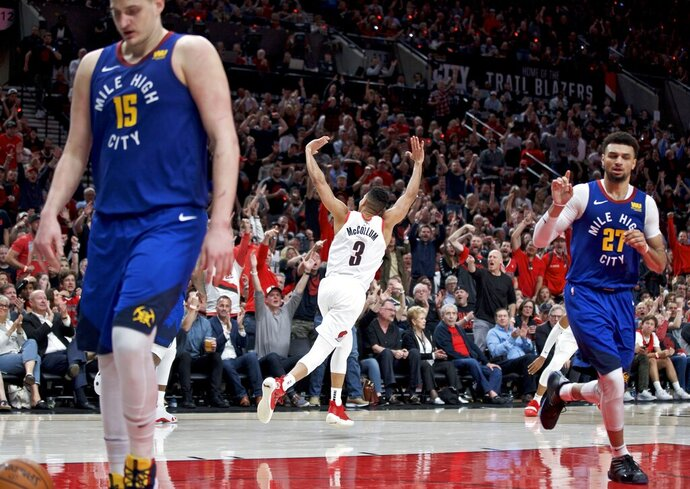 Portland Trail Blazers guard CJ McCollum, center, reacts after making a three point basket against the Denver Nuggets during overtime of Game 3 of an NBA basketball second-round playoff series Friday, May 3, 2019, in Portland, Ore. (AP Photo/Craig Mitchelldyer)