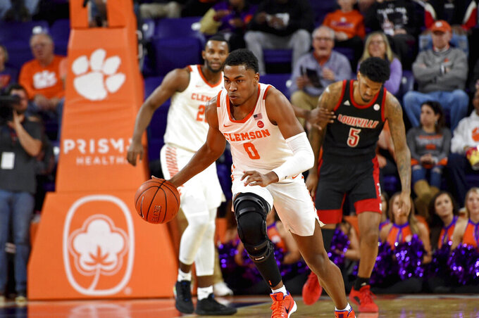 Clemson's Clyde Trapp, center, dribbles after a steal during the first half of an NCAA college basketball game against Louisville, Saturday, Feb. 15, 2020, in Clemson, S.C. (AP Photo/Richard Shiro)