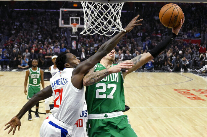 Boston Celtics forward Daniel Theis, right, shoots as Los Angeles Clippers guard Patrick Beverley defends during the second half of an NBA basketball game Wednesday, Nov. 20, 2019, in Los Angeles. (AP Photo/Mark J. Terrill)