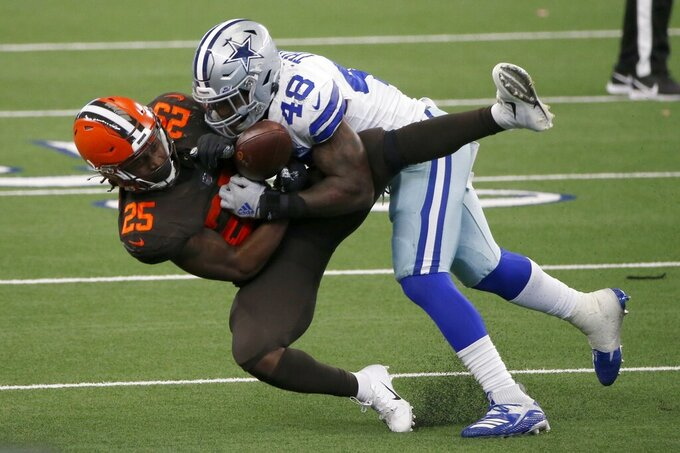 Cleveland Browns running back Dontrell Hilliard (25) catches a pass under pressure from Dallas Cowboys linebacker Joe Thomas (48) in the second half of an NFL football game in Arlington, Texas, Sunday, Oct. 4, 2020. (AP Photo/Michael Ainsworth)