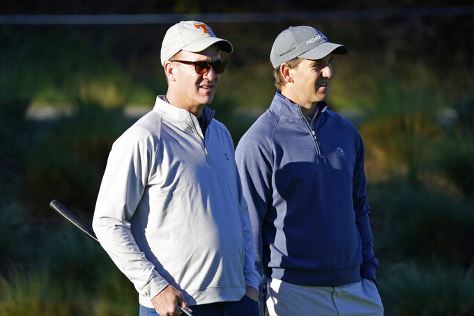 "FILE - In this Feb. 6, 2020 file photo, Peyton Manning, left, and his brother Eli Manning wait to hit from the first tee of the Spyglass Hill Golf Course during the first round of the AT&T Pebble Beach National Pro-Am golf tournament in Pebble Beach, Calif. Both Mannings have become deejays. The former quarterbacks, two-time Super Bowl-winning brothers and close mates with Kenny Chesney, kicked off the ""Poets & Pirates DJ Sessions"" this week on the singer's SiriusXM channel, No Shoes Radio. In addition to spinning the songs, the Mannings told stories about their personal meanings, as well as about their long-time friendships with Chesney. (AP Photo/Tony Avelar, File)"