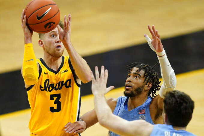 Iowa guard Jordan Bohannon (3) shoots over North Carolina's R.J. Davis, center, and Andrew Platek, right, during the second half of an NCAA college basketball game, Tuesday, Dec. 8, 2020, in Iowa City, Iowa. Iowa won 93-80. (AP Photo/Charlie Neibergall)
