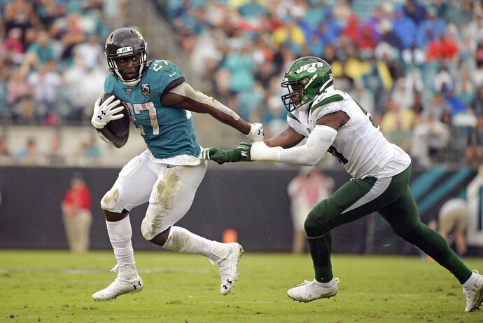 Jacksonville Jaguars running back Leonard Fournette (27) escapes a tackle by New York Jets outside linebacker Brandon Copeland, right, during the first half of an NFL football game, Sunday, Oct. 27, 2019, in Jacksonville, Fla. (AP Photo/Phelan M. Ebenhack)