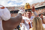 Texas quarterback Sam Ehlinger (11)   holds the Golden Hat as he celebrates with teammates after defeating Oklahoma 48-45 in an NCAA college football game at the Cotton Bowl, Saturday, Oct. 6, 2018, in Dallas. (AP Photo/Cooper Neill)