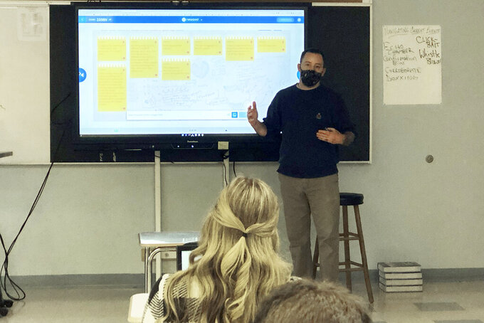 """Conor Murphy, a teacher at West Genesee High School, in Camillus, N.Y., conducts his """"Participation in Government"""" class, Thursday, Jan. 7, 2021.   Many teachers say they are treading cautiously in light of varied political viewpoints in their classrooms and communities. But they universally describe efforts to hear out students' fears and concerns. (Photo by A. Thomson via AP)"""