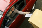 A voter drops off her ballot on the day of Oregon's primary election at a drive by drop-off station in Portland, Ore., Tuesday, May 15, 2018. (AP Photo/Don Ryan)