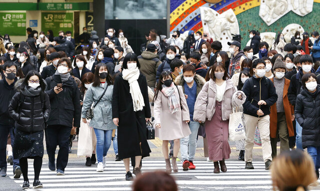 People wearing face masks to protect against the coronavirus make their way at an intersection in Tokyo Thursday, Dec. 24, 2020. The Japanese capital confirmed more than 800 new coronavirus cases on Thursday. (Masanobu Kumagai/Kyodo News via AP)