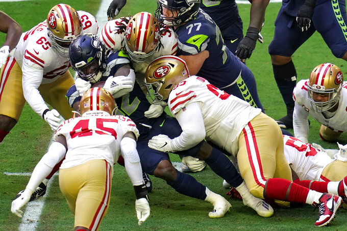 Seattle Seahawks running back Chris Carson (32) is stopepd by San Francisco 49ers defensive tackle D.J. Jones (93), middle linebacker Fred Warner (54) and defensive tackle Darrion Daniels (65) during the first half of an NFL football game, Sunday, Jan. 3, 2021, in Glendale, Ariz. (AP Photo/Ross D. Franklin)
