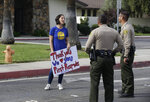 Santa Clarita resident Veronica Candy thanks Los Angeles Sheriff deputies outside the Saugus High School in Santa Clarita, Calif., Friday, Nov. 15, 2019. A homicide official says that investigators did not find a diary, manifesto or note belonging to the boy who killed two people outside his Southern California high school on his 16th birthday. Officials held a press conference Friday outside of the police station Santa Clarita. No motive or rationale has been established yet in the Thursday morning shooting at Saugus High School in the Los Angeles suburb of Santa Clarita. (AP Photo/Damian Dovarganes)