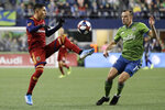 Real Salt Lake forward Jefferson Savarino, left, kicks the ball as Seattle Sounders defender Brad Smith, right, defends during the first half of an MLS Western Conference semifinal playoff soccer match Wednesday, Oct. 23, 2019, in Seattle. (AP Photo/Ted S. Warren)