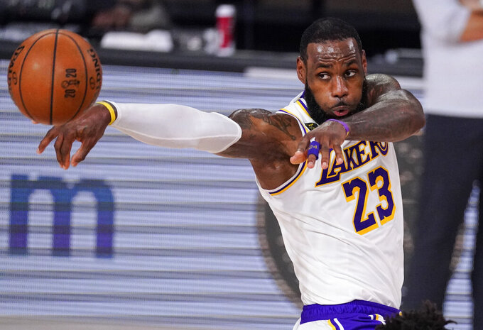 FILE - In this Oct. 4, 2020, file photo, Los Angeles Lakers' LeBron James (23) passes the ball against Miami Heat during the first half in Game 3 of basketball's NBA Finals in Lake Buena Vista, Fla.  James was announced Saturday, Dec. 26,  as the winner of The Associated Press' Male Athlete of the Year award for a record-tying fourth time. (AP Photo/Mark J. Terrill, File)